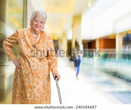 Old woman with a cane in the shopping mall - stock photo