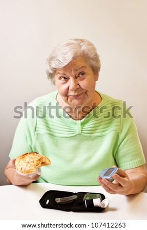 old woman with bun and blood glucose meter - stock photo