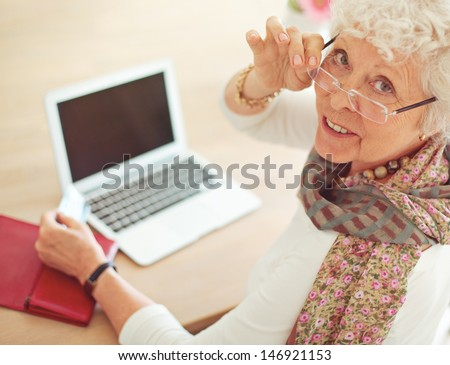 Old woman with credit card in front of her laptop looking at you - stock photo