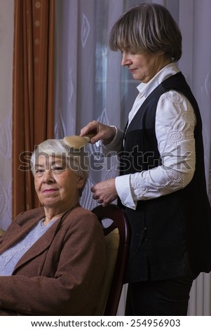 Old woman with her daughter - stock photo