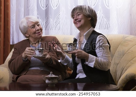 Old womanwith a cup of tea with a daughter. - stock photo