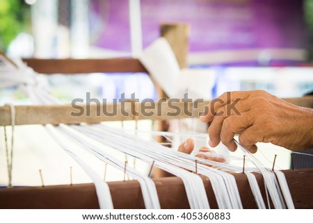 Old women hand holding white  thread on Loom in north Thailand - stock photo