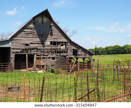 old wood barn by a rusty fence in rural Kansas  - stock photo