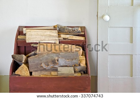 Old Wood Box Holding Firewood Beside Door in House - stock photo