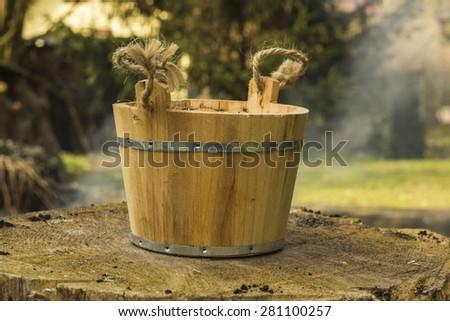 Old wood bucket on the stump - stock photo