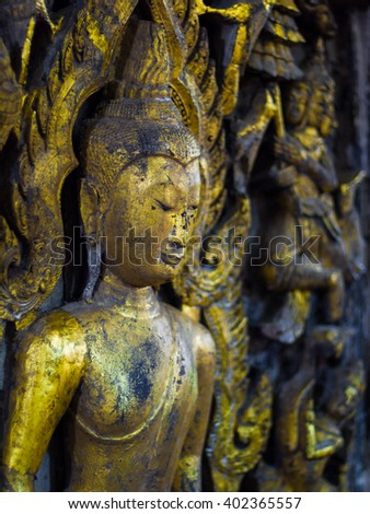 Old wood Buddha statues Cover with gold. Background blur. - stock photo