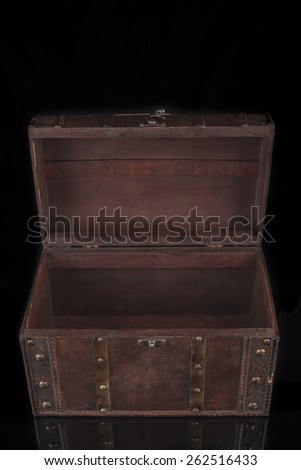 Old wood chest closed isolated on black background with reflection - stock photo