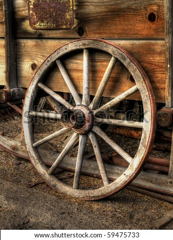 old wood coach wheel around barn - HDR - stock photo