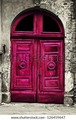 Old wood red door with damaged brick wall - stock photo