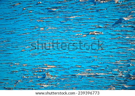 Old wood surface with blue paint flaking and cracking background texture - stock photo