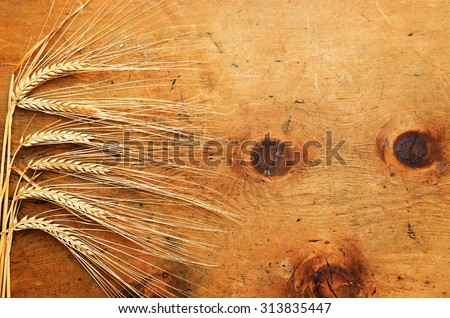 Old wood table with spikelets of wheat makes a frame for a text in rustic vintage style. Top view. Retro concept background. For poster, menu and recipe. - stock photo