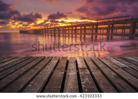 old wood terrace on sea beach during sunset - stock photo
