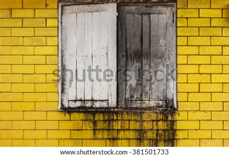 Old wood window on a yellow brick wall, stains wall - stock photo