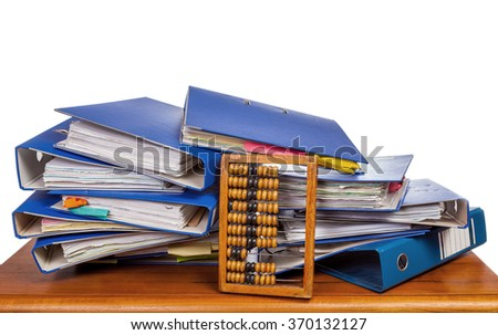 Old wooden abacus by pile of an office folders on brown table over white background - stock photo