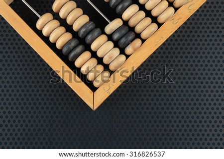Old wooden abacus on a metallic background with perforation of round holes - stock photo
