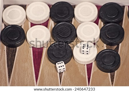 Old wooden backgammon board with pieces - stock photo