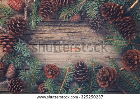 Old wooden background with pine cones fir-tree branches. Christmas decoration.Toned image. Vintage style. Copy space. selective focus.  - stock photo
