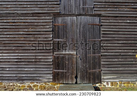Old wooden barn entrance door with rusting hinges and a total weathered look - stock photo