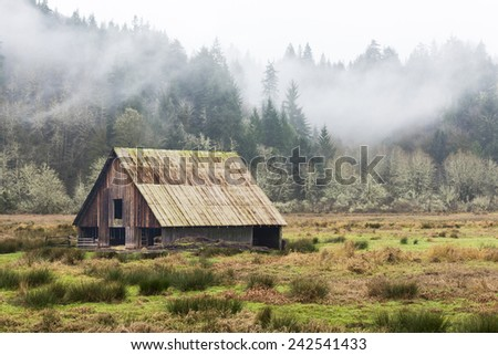 Old wooden Barn in Field, Mountains, Trees and Clouds - stock photo