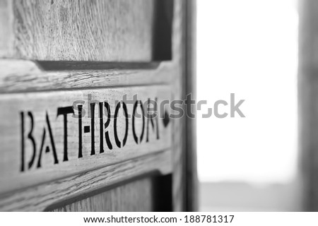 Old wooden bathroom door with shallow depth of field - stock photo
