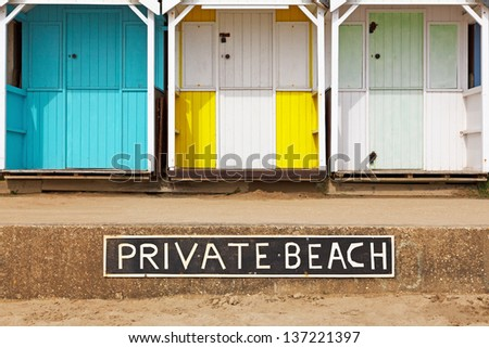 Old wooden beach huts on a Private beach with sign - stock photo