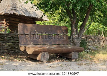 Old wooden bench and wicker fence. Ukraine, Pirogovo - stock photo