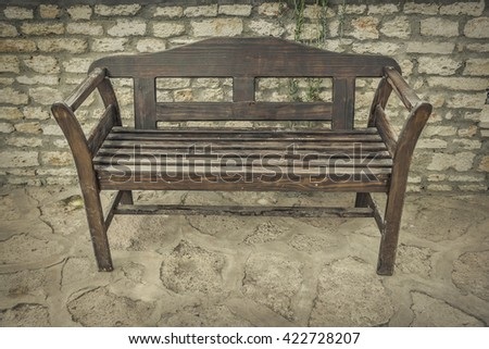 Old wooden bench on a stone background. Toned photo. - stock photo