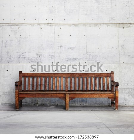 Old wooden bench on bright concrete background - stock photo