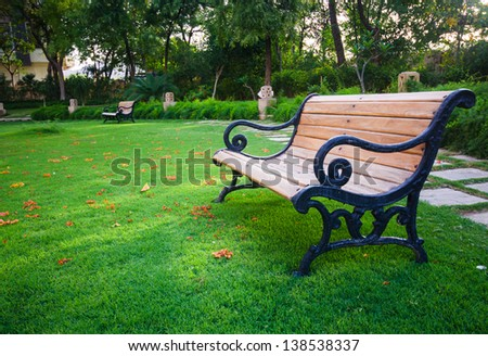 old wooden bench on green meadow - stock photo