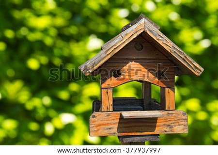 Old wooden birdhouse on a green blurred background - stock photo