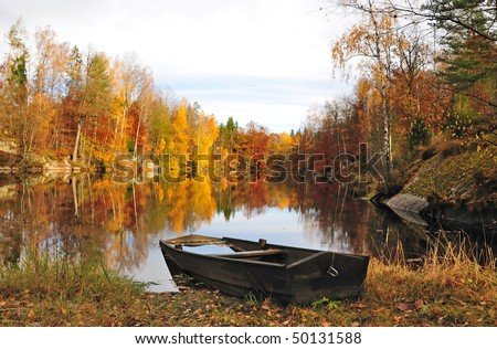 Old wooden boat on the lake bank in autumn season - stock photo