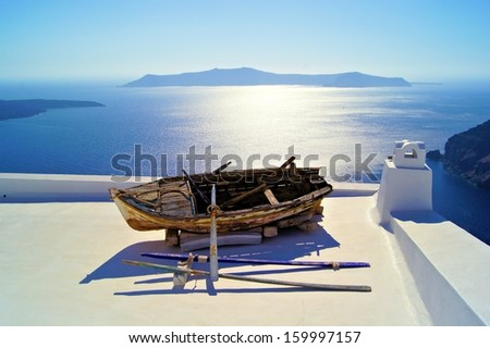 Old wooden boat resting on the white rooftops of Santorini, Greece - stock photo