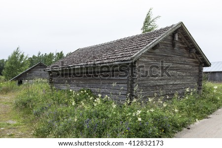 Old wooden boathouse, warehouse surrounded by flowers. Gravel road to the right. - stock photo