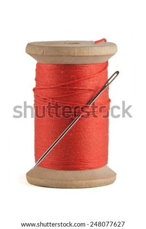 Old wooden bobbin with red thread isolated on white - stock photo