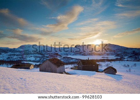Old wooden cabin in the snow coverd mountain, colored by the sunset - stock photo