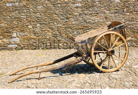 Old wooden carriage on the pavement and rough stone wall at background. - stock photo
