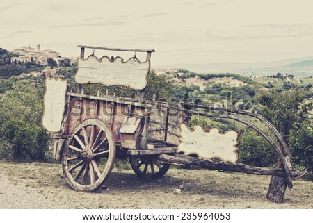 Old wooden cart against vineyards, Tuscany, Italy. Processing in retro style - stock photo