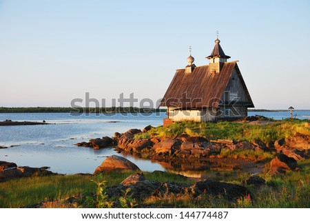 Old wooden church on sunset near White Sea, Russia North - stock photo