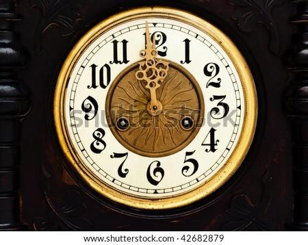 old wooden clock with  golden hands show twelve - stock photo