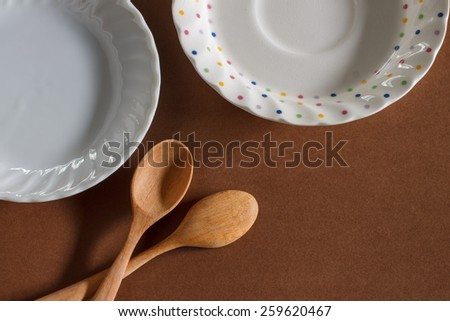 old wooden cooking spoon with small plate put on brown paper background - stock photo