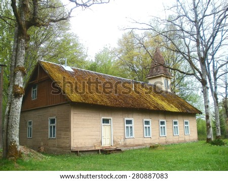 Old wooden country church with mossy asbestos roof near forest       - stock photo