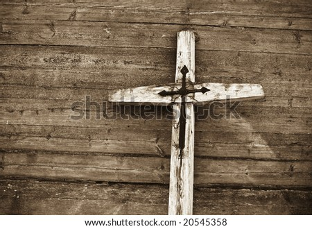 Old wooden cross against wooden background. Sepia tone. - stock photo