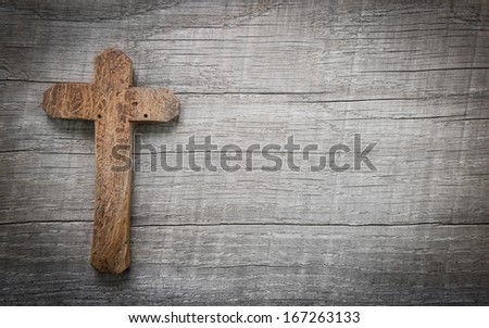 Old wooden cross on a wooden background with copy space for a condolence text. - stock photo