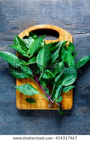 Old wooden cutting board with thai basil on dark rustic background, top view. Simple food concept. - stock photo