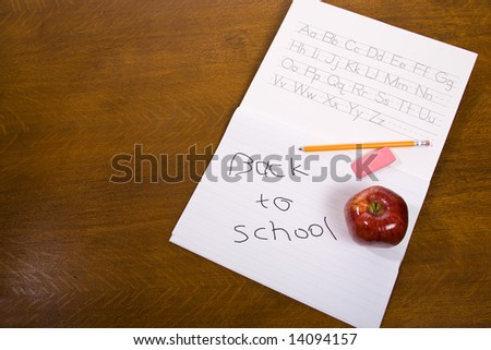Old Wooden desk with pencil, eraser, and apple on alphabet book. - stock photo