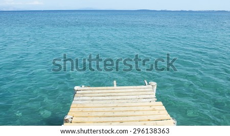 Old wooden dock and blue sea - stock photo