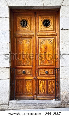 Old wooden door in a stone wall with a round window. Sintra. Portugal. - stock photo