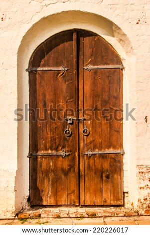 Old wooden door in ancient painted brick wall - stock photo