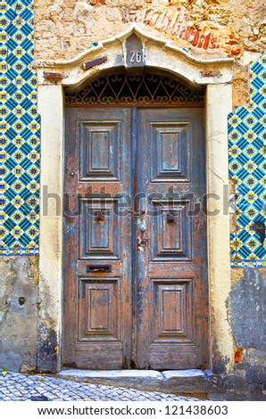 Old wooden door in Portugal. Wall of traditional Portuguese tiles - stock photo