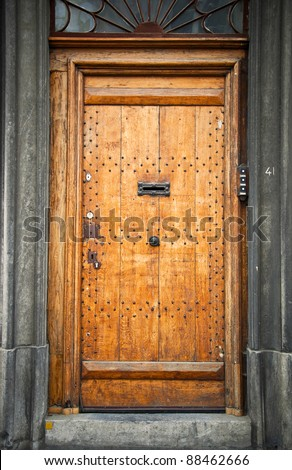 Old wooden door in the town of Mons. Belgium. Fragment, close-up. - stock photo